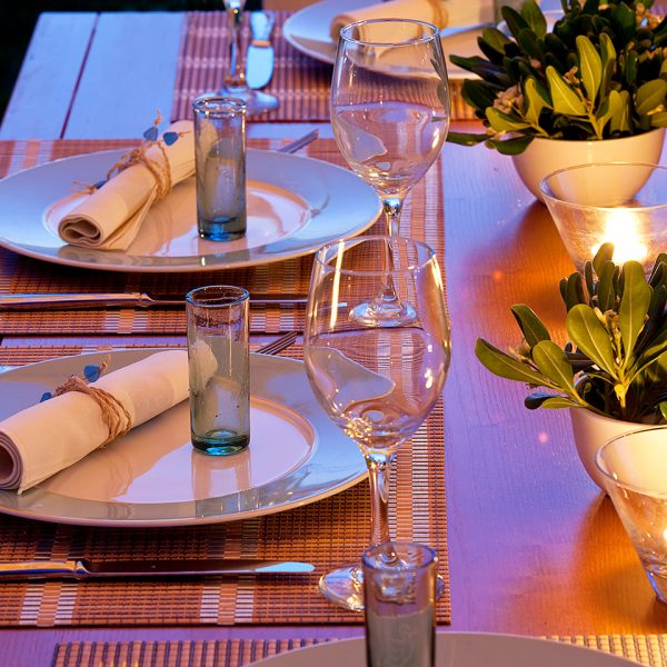 Plates, glasses, candles & cutlery on dining tables at Yria luxury Hotel & Spa restaurant in Paros