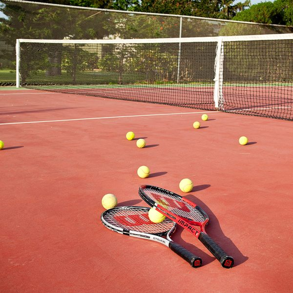 Tennis racquets & balls on the clay tennis court at Yria Island Boutique Hotel resort & Spa in Paros