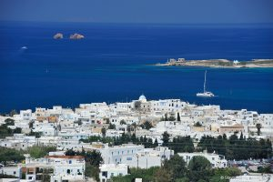 View of a traditional whitewashed seaside island town in Paros, Greece & a boat in the sea