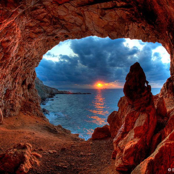 Sunset seen from a cave by the Agios Fokas beach opposite Yria Island Hotel in Parasporos Bay, Paros