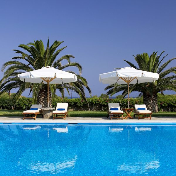 View of pool, sunbeds, tables, umbrellas & palm trees at Yria Hotel Paros with sea in the background