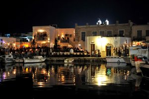Boats & people in crowded harbour of Parikia at night It is capital of the island of Paros, Greece