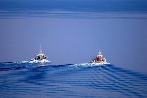 Two fishing boats in the sea near Paros, Greece, where the Yria Island Boutique Hotel & Spa is based