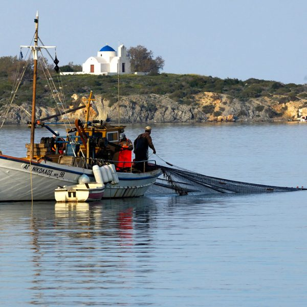 Fisherman fish from a boat in the sea off Paros. This greek holiday island is home to Yria Hotel