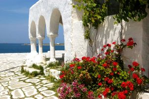 Flowers by traditional Cycladic style building with archways, overlooking the sea in Paros, Greece