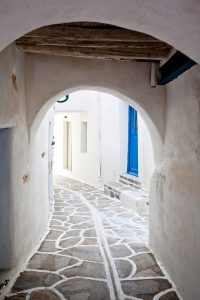 Archway over charming cobbled alleyway in a town in Paros with traditional Cycladic architecture