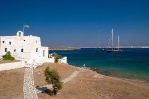 Whitewashed Cycladic style building with bell tower & blue shutters by the coast in Paros, Greece