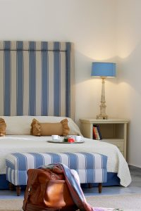 Stylish Junior Suite bedroom at Yria Boutique Hotel in Paros, with king size bed, pillows & table