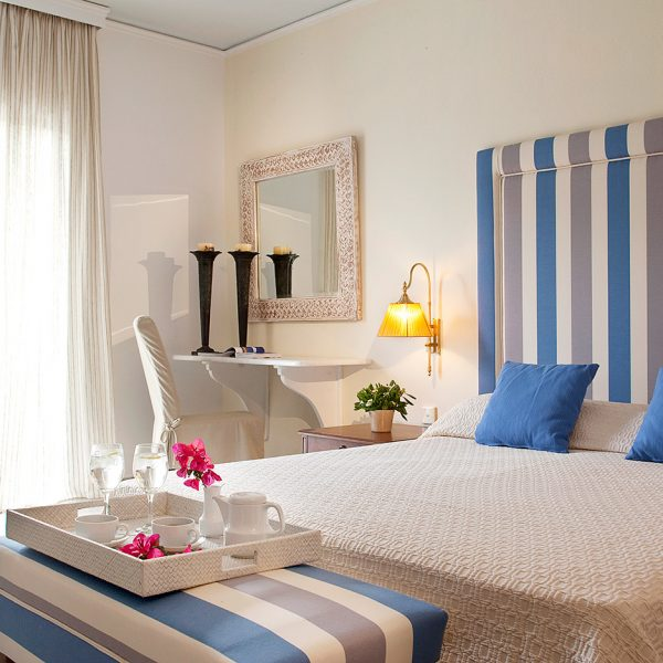 Tea tray at foot of the bed in airy luxury bedroom of Yria Hotel & Spa family Maisonette in Paros
