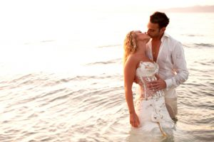 Newly married couple kiss on Parasporos beach after a wedding at Yria Hotel & Spa resort in Paros