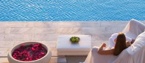 Resting in a chair at dusk beside the swimming pool at Yria Island Luxury Hotel in Paros