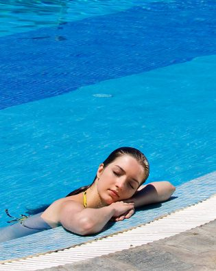 Lady rests beside private pool in the Yria Hotel Pool Experience Suite accommodation in Paros