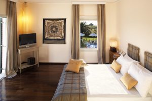King size bed in family Residence Suite bedroom overlooking Yria Hotel pool near Parikia, Paros
