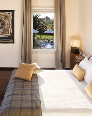 Bed by window in luxury bedroom of Yria Island Hotel sea view Residence Suite accommodation in Paros