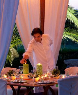 Waiter lights candles at the Nefeli fine dining restaurant at Yria Island Hotel & Spa in Paros
