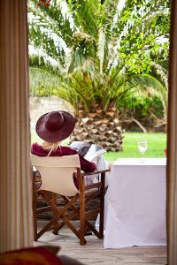 Lady sits in a chair by table on the garden view veranda of Yria Hotel Superior Double Room in Paros