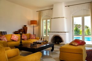 Luxury living room of the Yria Villa in Paros, with fireplace, & patio doors to private pool area