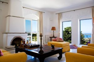 Yria Paros Villa living room with fireplace, coffee table, chairs & Parasporos bay sea view windows