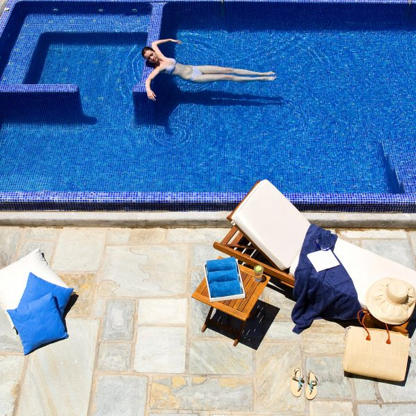 Woman in the Yria Villa private pool in Paros, with sunbed, table, drink, towels & pillows beside