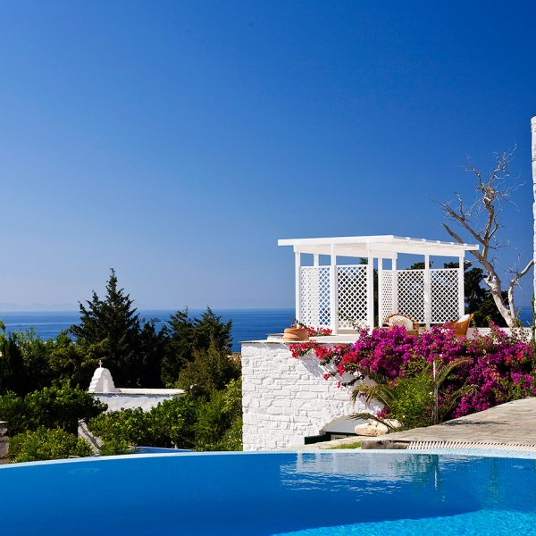 View of the sea, tops of trees & chapel from outdoor area of Yria Ktima private pool villa in Paros