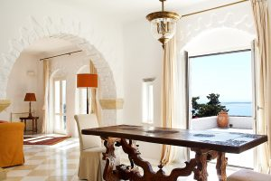 Table in open plan dining area of Yria luxury Villa in Paros next to open doors to sea view veranda