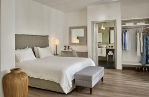 Bedroom area of Yria Hotel Executive luxury couples Suite in Paros with king size bed & footstool