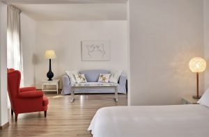 Bed by ensuite living area of the 2 person Private Pool Experience Suite at Yria Hotel in Paros