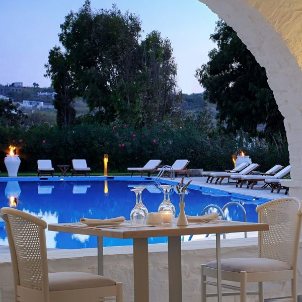 Restaurant dining table overlooking dusk view of Yria luxury hotel pool, sunbeds & Paros countryside