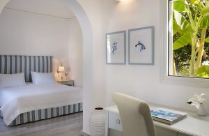 Junior Suite chair & writing desk, & archway to bedroom with king size bed at Yria Hotel in Paros