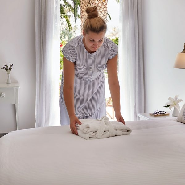 Maid at Yria Island Boutique Hotel & Spa folds robe on the bed of the Superior Double Room in Paros
