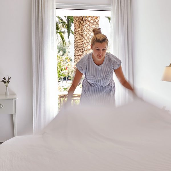 Yria Boutique Hotel maid makes the bed of the family Maisonette in Paros by open door to veranda