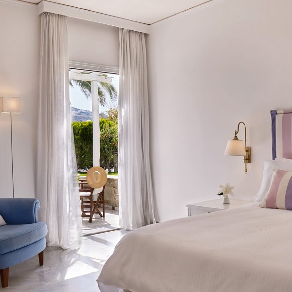 Bed by open patio doors to garden view veranda of Yria Hotel luxury Superior Double Room in Paros