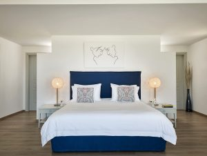 King size bed, pillows, lamps, tables & art print in luxury 2 person Pool Experience Suite in Paros