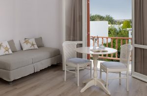 Paros Executive couples Suite lounge living area with table, chairs & sofa by private veranda