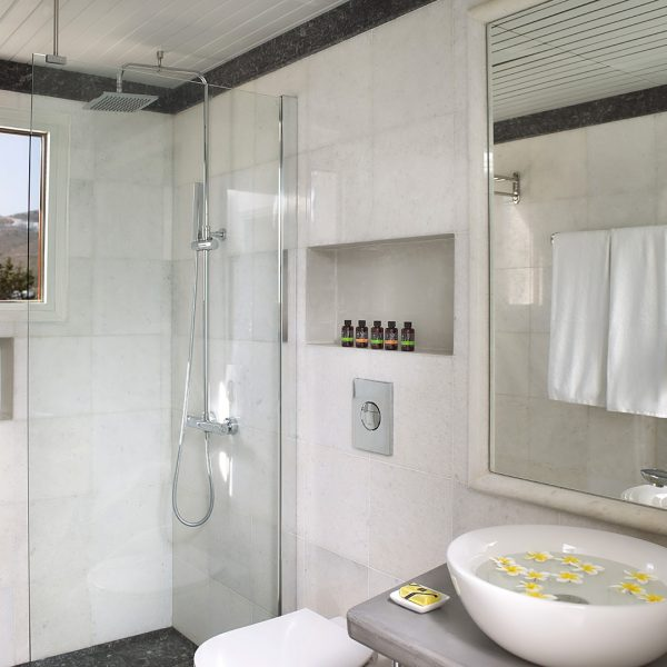 Shower, sink, mirror, towels, toiletries & robe in luxury bathroom of family Maisonette in Paros