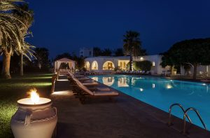 Nighttime in Paros island. Lights illuminate Yria Hotel Resort & Spa building & swimming pool area