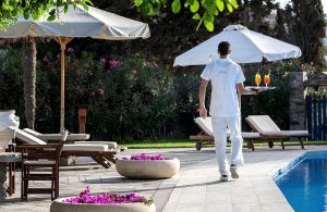 Yria Luxury Boutique Hotel & Spa waiter walks beside pool with drinks from the resort bar in Paros