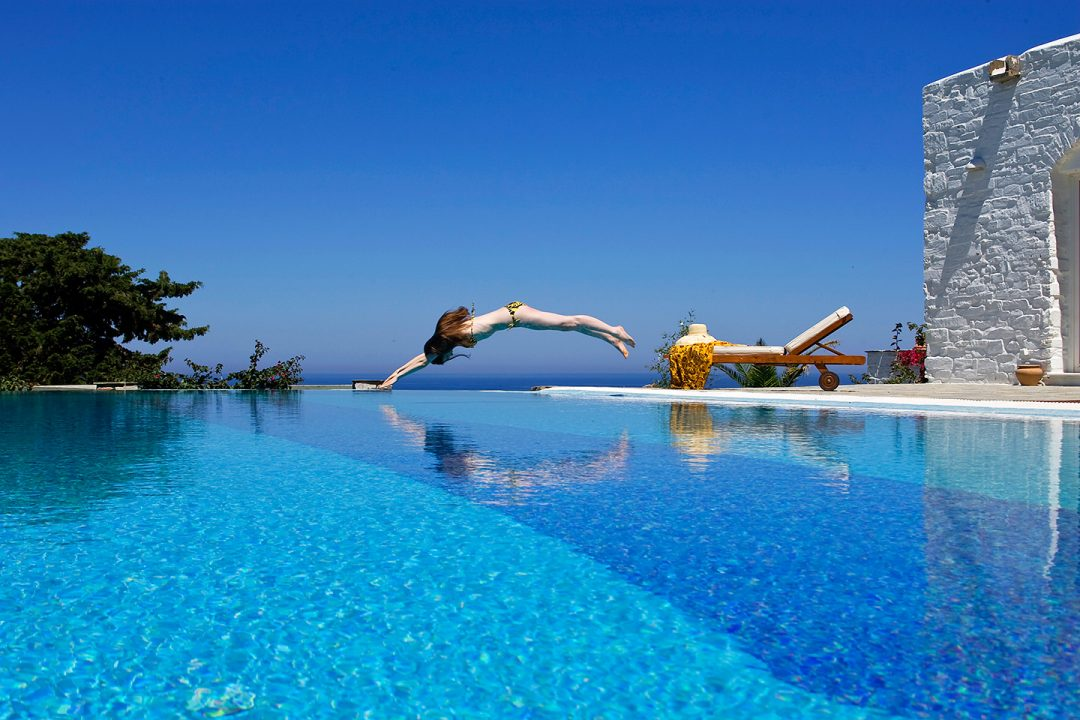 A lady traveller dives into a pool during a holiday in Paros as Yria Island Boutique Hotel & Spa
