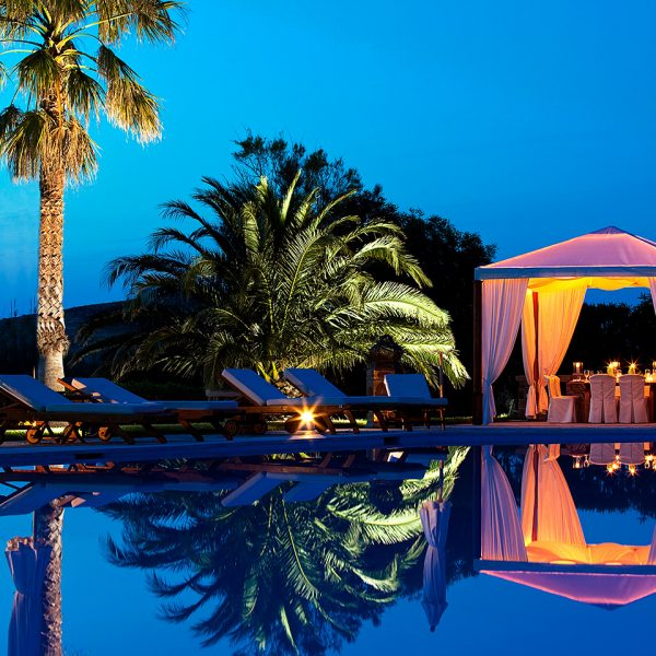 Yria luxury Hotel pool & restaurant outdoor dining area in Paros at night. Lights illuminate trees