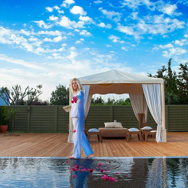 Yria Paros Hotel Spa staff member drops rose petals in the plunge pool, with spa pavilion behind