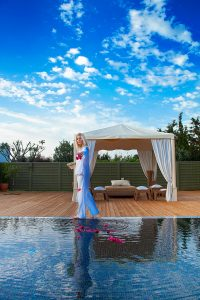 A member of the Yria Paros Boutique Hotel team scatters petals in the luxury spa plunge pool Jacuzzi