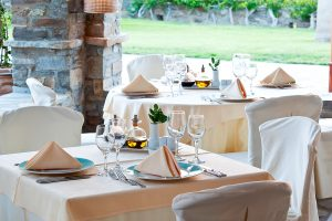 Tables & chairs ready for lunch in Nefeli restaurant by Yria Luxury Island Hotel gardens in Paros