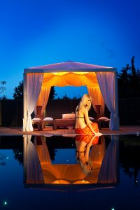 A lady sits by the edge of the Paros Hotel spa plunge pool at Yria Boutique Hotel Resort at dusk