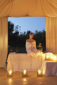 Lady in robe ready for her spa treatment in the Yria Hotel pavilion in Paros, surrounded by candles