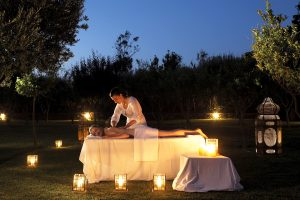 A relaxing massage lit by candlelight in the gardens at Yria Paros luxury Boutique Hotel Spa