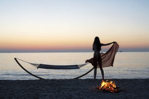 Guest at Yria Island Boutique Hotel resort in Paros uses a hammock on Parasporos beach at sunset