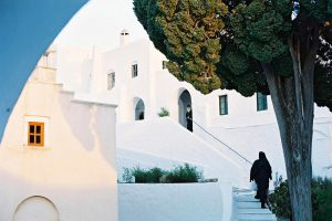 Nun walks up stairs towards priest in monastery building on the Cyclades island of Paros, Greece