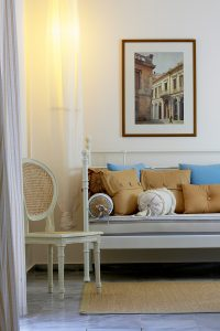 Sofa, chair & painting in lounge area of 2 floor family Maisonette at Yria luxury Hotel in Paros
