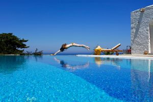 Lady dives into the private pool next to the whitewashed luxury Villa in Paros at Yria Island Hotel