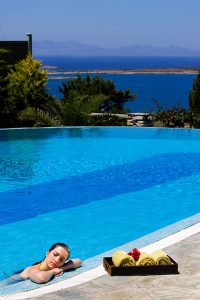 Lady resting by edge of Yria villa private pool with towels by her. Paros sea view in background